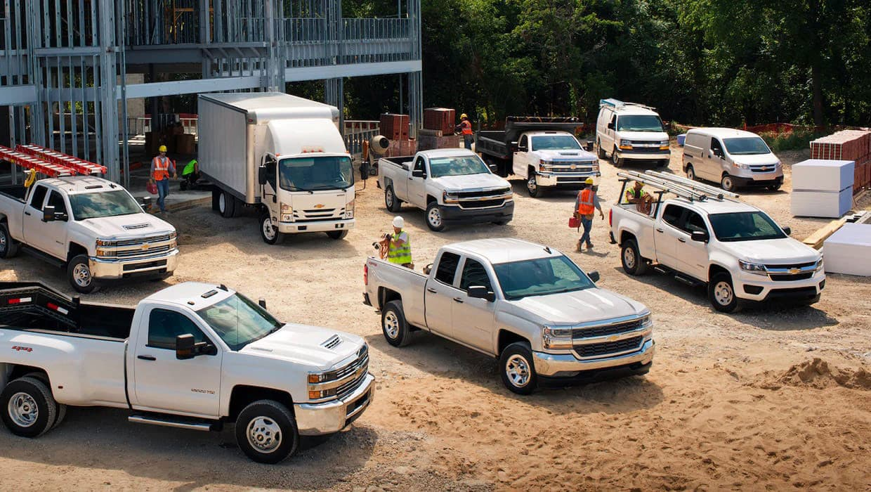 9 Chevrolet Commercial Vehicles parked outside construction site.